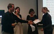 Master of ceremony David Kaplan (left) hands over first prize to winner Rebecca Gelding (right) at the 3MT competition